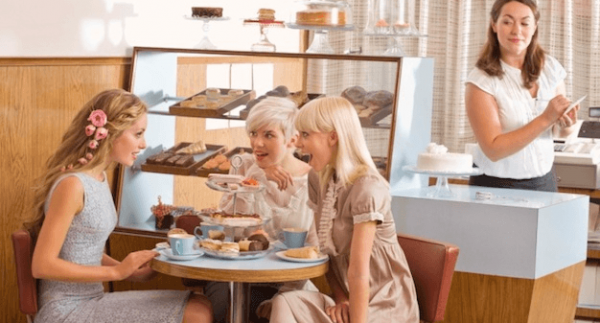 Three ladies having tea with dainties and employee eavesdropping on their conversation